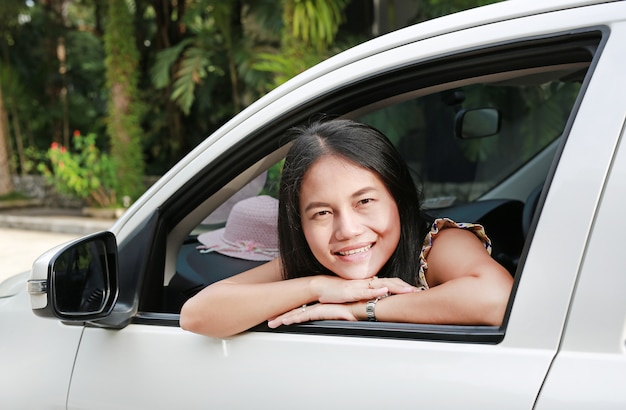 Belle jeune femme asiatique dans une voiture