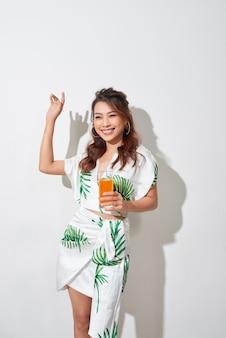 Belle jeune femme asiatique avec du jus d'orange en chemise tropicale sur fond blanc