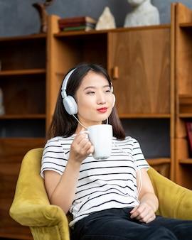 Belle jeune femme asiatique, écouter de la musique avec des écouteurs, assis dans une chaise