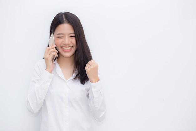 Belle jeune femme asiatique excitée et heureuse de succès prenant le téléphone portable.