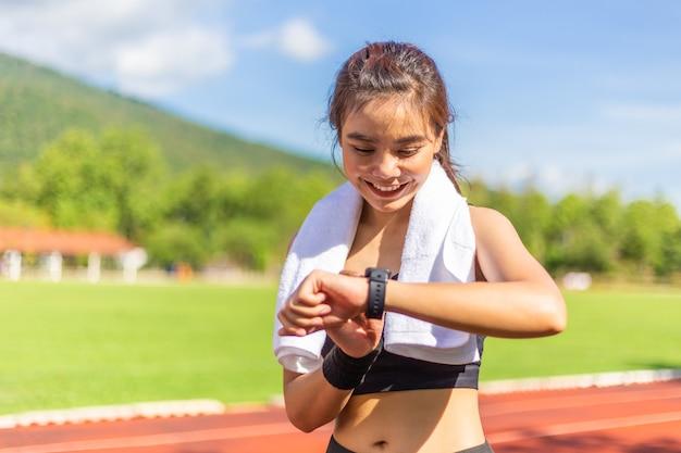 Belle jeune femme asiatique exerçant le matin sur une piste de course