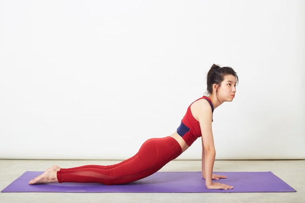 Belle jeune femme asiatique faisant cobra pose sur un tapis de yoga à la maison, concept de vie saine et équilibre naturel entre le corps et le développement mental