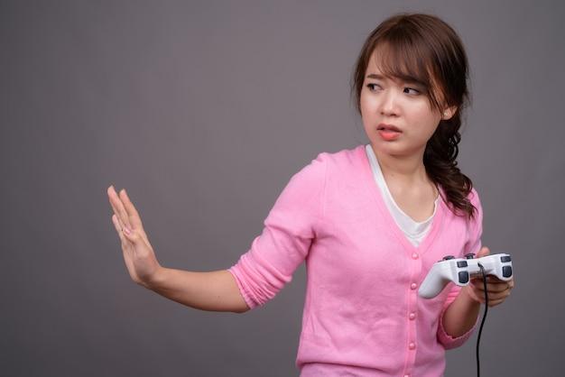 Belle jeune femme asiatique jouant à des jeux avec contrôleur de jeu