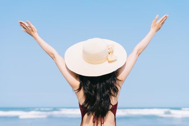Belle jeune femme asiatique en maillot de bain se détendre à la plage pendant les vacances d'été