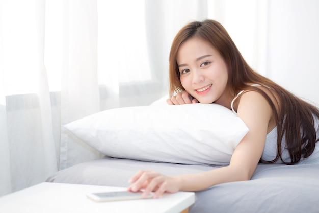 Belle jeune femme asiatique main d'éteindre l'alarme sur appel téléphone mobile