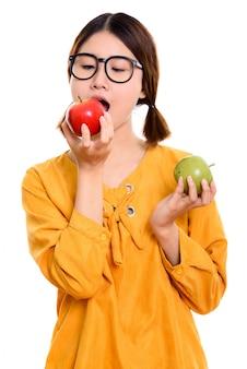 Belle jeune femme asiatique mangeant une pomme rouge tout en tenant une pomme verte