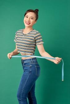 Belle jeune femme asiatique mesurant sa taille avec un ruban à mesurer sur vert