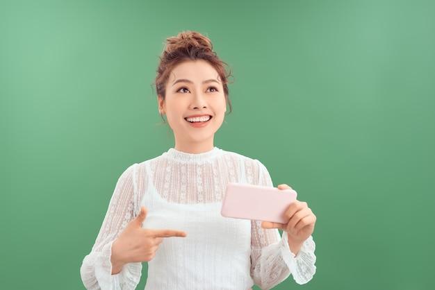 Belle jeune femme asiatique montrant un téléphone portable en se tenant debout et en levant isolé sur fond vert.