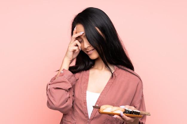Belle jeune femme asiatique sur mur rose tenant des sushis