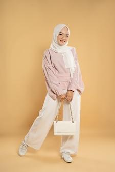 Belle jeune femme asiatique musulmane, sur un fond clair isolé, habillée dans le style moderne hijab