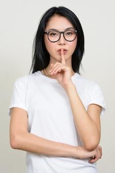 Belle jeune femme asiatique nerd portant des lunettes isolées