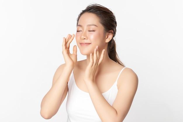 Belle jeune femme asiatique avec une peau fraîche et propre, sur fond rose, soins du visage, traitement du visage. cosmétologie, beauté et spa. portrait de femmes asiatiques