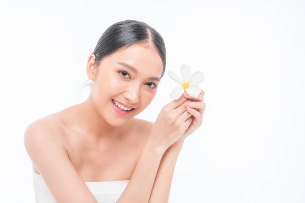 Belle jeune femme asiatique à la peau propre, peau fraîche tenant une feuille tropicale de fleur blanche dans les mains sur fond blanc - photo de beauté d'une femme asiatique traitement du visage, cosmétologie, beauté et spa