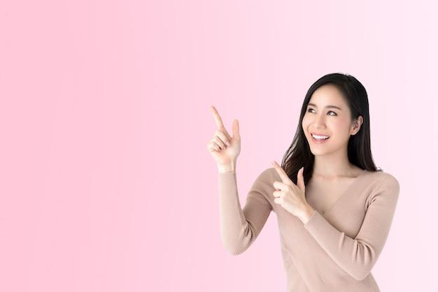 Belle jeune femme asiatique, pointant les mains pour vider l'espace de côté