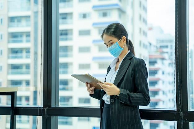 Belle jeune femme asiatique portant un masque de protection pour se protéger contre covid-19 travaillant au bureau dans un bureau moderne.