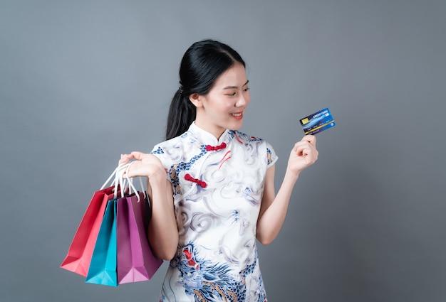 Belle jeune femme asiatique porte une robe traditionnelle chinoise avec sac à provisions et carte de crédit sur fond gris