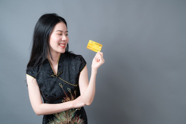 Belle jeune femme asiatique porter une robe traditionnelle chinoise noire avec une main tenant une carte de crédit sur un mur gris