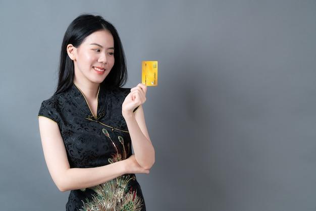 Belle jeune femme asiatique porter une robe traditionnelle chinoise noire avec une main tenant une carte de crédit sur une surface grise