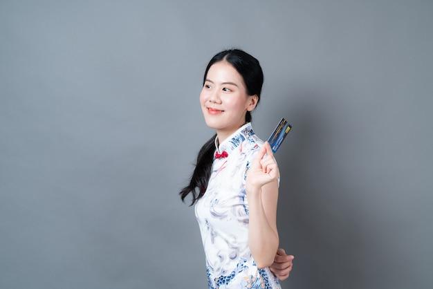 Belle jeune femme asiatique porter des vêtements traditionnels chinois avec une main tenant une carte de crédit sur un mur gris