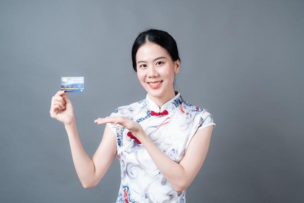 Belle jeune femme asiatique porter des vêtements traditionnels chinois avec une main tenant une carte de crédit sur une surface grise