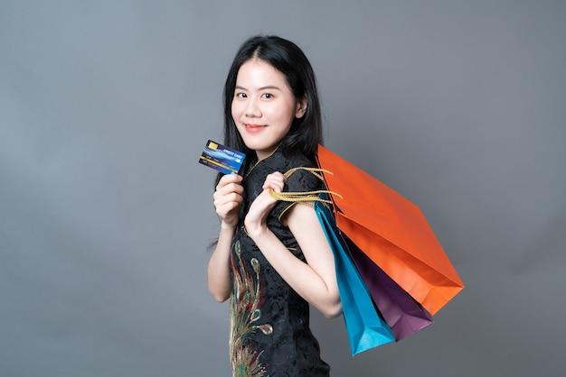 Belle jeune femme asiatique porter des vêtements traditionnels chinois avec sac à provisions et carte de crédit sur mur gris