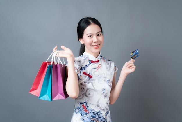 Belle jeune femme asiatique porter des vêtements traditionnels chinois avec sac à provisions et carte de crédit sur surface grise
