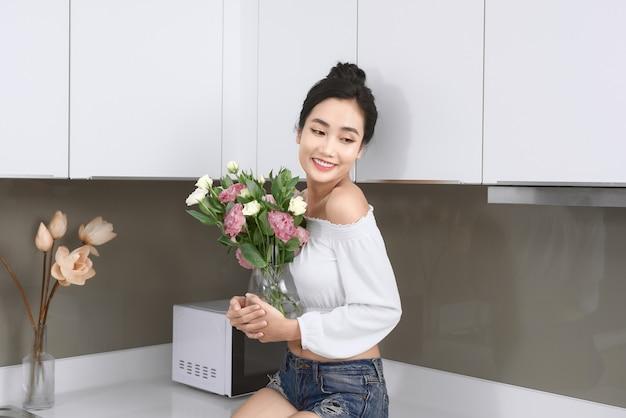 Belle Jeune Femme Asiatique Posant Avec Fleur Dans La Cuisine. Photo Premium