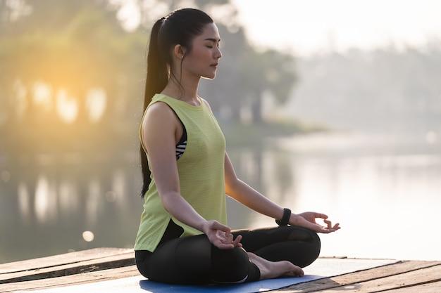 Belle jeune femme asiatique pratiquant le yoga et méditant dans la pose de lotus en plein air au bord du lac le matin pour la détente et la tranquillité d'esprit. concept d'harmonie et de méditation. mode de vie sain