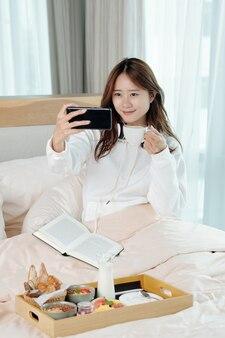 Belle jeune femme asiatique prenant son petit déjeuner au lit, elle prend un selfie ou filme une vidéo avec une tasse de café à la main