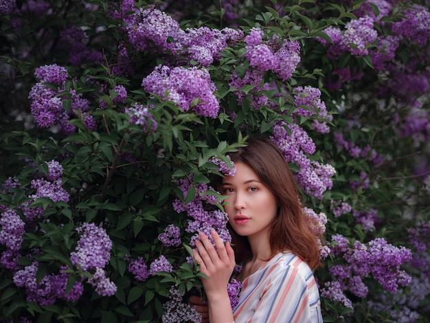 Belle jeune femme asiatique profitant de la floraison des fleurs lilas au printemps. maquillage nu. portrait en gros plan