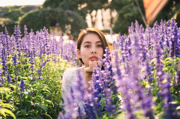 Belle jeune femme asiatique en robe blanche appréciant dans le champ de lavande sous le soleil