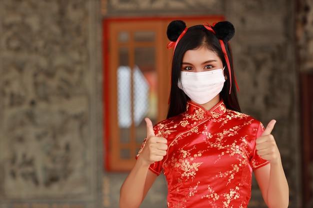 Belle jeune femme asiatique en robe chinoise rouge traditionnelle cheongsam qipao porter un masque de protection pour les soins de santé avec un geste montrant le pouce vers le haut ou double comme (nouveau concept normal et nouvel an chinois)