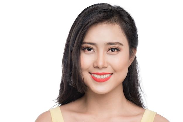 Belle jeune femme asiatique en robe jaune debout sur blanc.