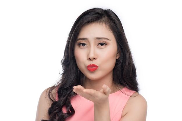 Belle jeune femme asiatique en robe rose soufflant sur blanc.