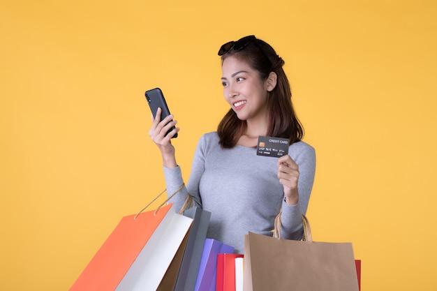 Belle jeune femme asiatique avec des sacs colorés avec téléphone intelligent et carte de crédit isolé sur mur jaune