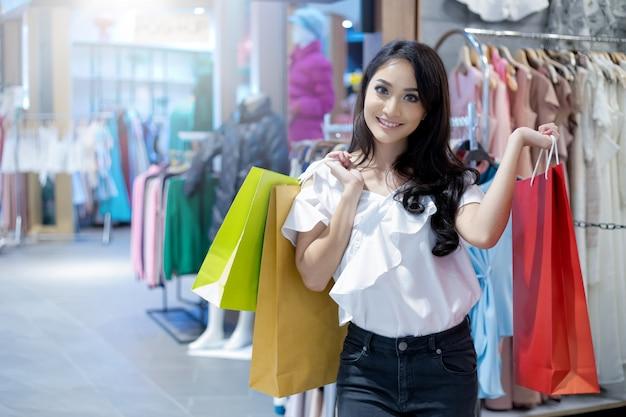 Belle jeune femme asiatique avec des sacs à provisions avec sourire en se tenant debout dans le magasin de vêtements. concept de bonheur, de consommation, de vente et de personnes