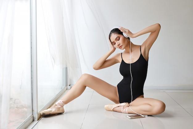 Belle jeune femme asiatique saine et sportive sportswear noir avec un casque, à l'aide de téléphone portable tout en pratiquant le ballet