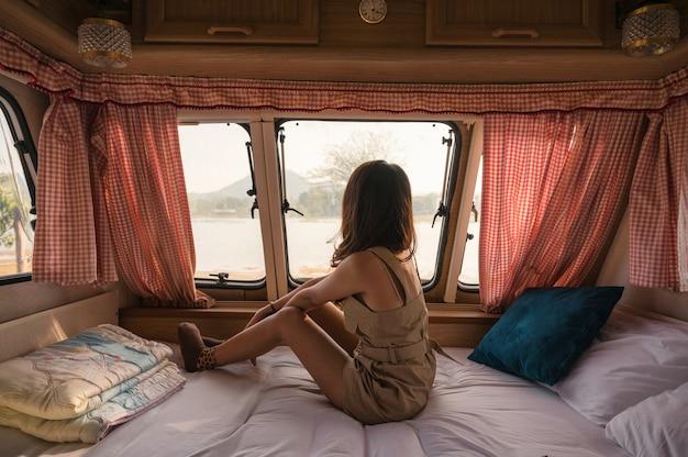 Belle jeune femme asiatique se détendre et regarder la vue en camping-car sur camping le soir