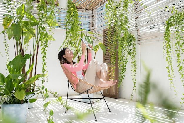 Belle jeune femme asiatique se relaxant et utilisant une tablette numérique à la maison