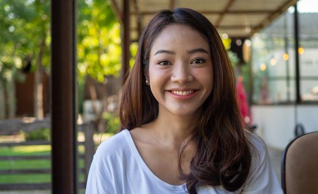 Une belle jeune femme asiatique se sent heureuse, souriante et détendue devant la caméra dans un café. fille asiatique souriante