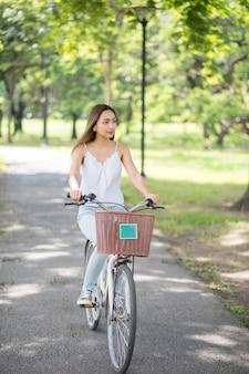 Belle jeune femme asiatique séduisante faisant du vélo en journée ensoleillée au parc du printemps de la ville. fille de vélo urbain avec fond de verdure plante arbre