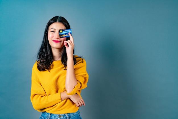 Belle jeune femme asiatique souriant et présentant une carte de crédit en main montrant la confiance et la confiance pour effectuer le paiement sur bleu