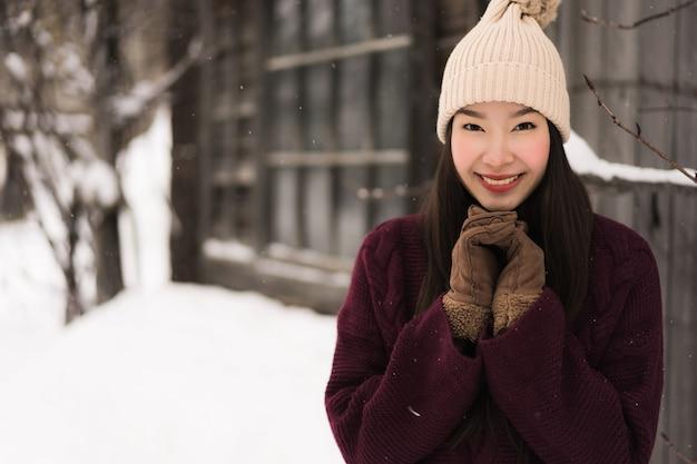 Belle jeune femme asiatique souriante heureuse de voyager dans la neige en hiver