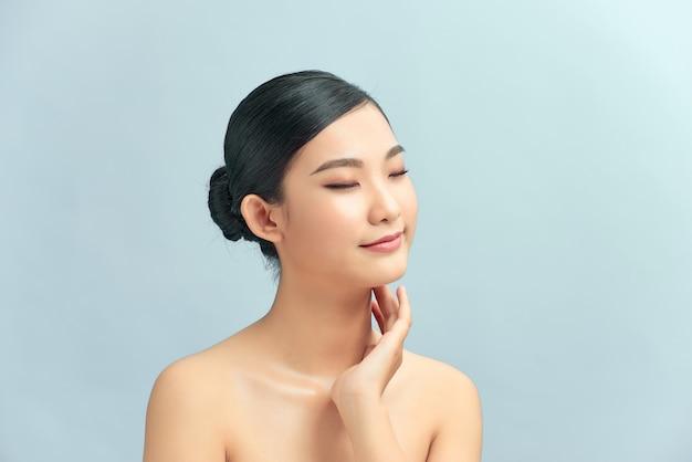 Belle jeune femme asiatique souriante et touchant son cou. isolé sur fond clair.