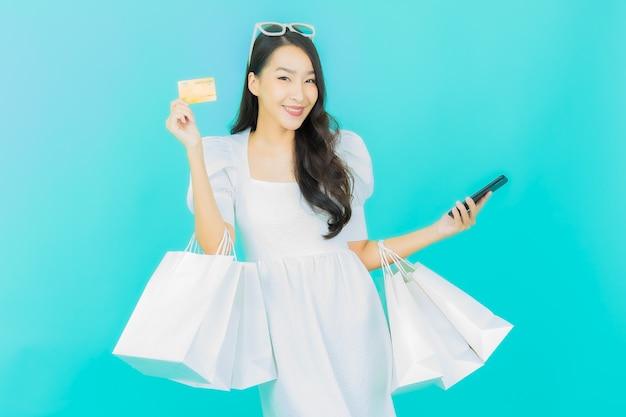 Belle jeune femme asiatique sourire avec panier sur bleu