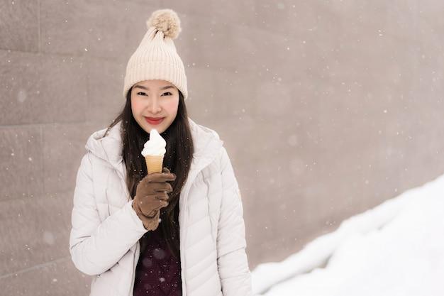 Belle jeune femme asiatique sourit et heureuse avec la crème glacée en hiver