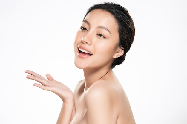 Belle jeune femme asiatique sourit de se sentir si heureux et joyeux. avec une peau saine et propre et fraîche. isolé sur blanc. beauté cosmétiques