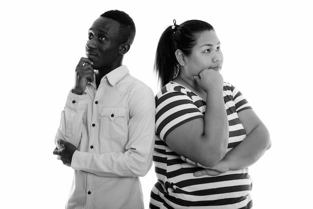 Belle jeune femme asiatique en surpoids et jeune homme africain ensemble en couple en noir et blanc