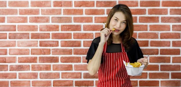 Belle jeune femme asiatique en tablier rayé rouge tenant un tamis de délicieuses pommes de terre frites près d'un mur de briques et le montre fièrement avec le sourire comme satisfaisant ses compétences culinaires et persuade de manger de la nourriture délicieuse