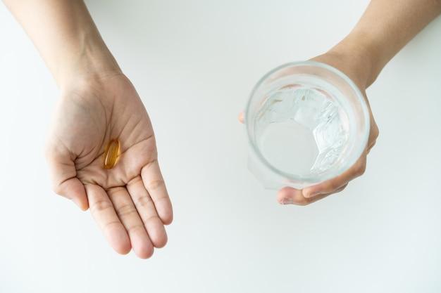 Belle jeune femme asiatique tenant une capsule d'huile de poisson sur sa main et tenant une eau potable dans un verre en gros plan. produit de suppléments nutritionnels et vitaminiques. pilule molle de gel sur la main de la femme.